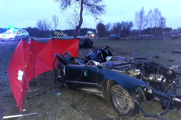 Rozkawałkowane auto leżało na przydrożnym polu.